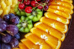 Assorted fruits with oranges, kiwis, grapes, cherries. The concept of healthy food and vegetarian. royalty free stock image