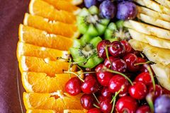 Assorted fruits with oranges, kiwis, grapes, cherries and pineapples. The concept of healthy food and vegetarian. stock images
