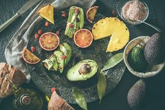 Assorted fruits on a plate. Avocados, blood oranges, kiwis, pineapple and strawberries royalty free stock photos