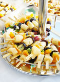 Assorted fruits on skewers on a stand Royalty Free Stock Photo