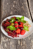 Assorted garden berries on a plate on wooden  background Royalty Free Stock Images