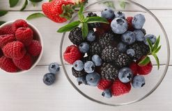 Mixed berries in glass bowls closeup, top view. Assorted garden and wild berries. Mix of fresh organic strawberries, raspberries, blueberries and blackberries in Royalty Free Stock Image