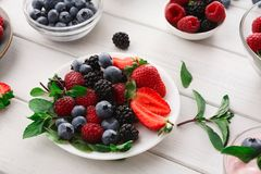 Mixed berries in glass bowls on white wooden table Royalty Free Stock Photos