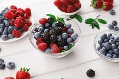 Mixed berries in glass bowls on white wooden table. Assorted garden and wild berries. Mix of fresh organic strawberries, raspberries, blueberries and Stock Images