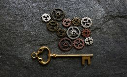 Gears and key. Assorted gears with gold key on dark textured background Royalty Free Stock Photo