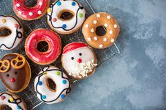 Assorted of glazed Christmas and New Year donuts on grey table. Flat lay stock image