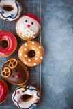 Assorted of glazed Christmas and New Year donuts on grey table. Flat lay stock photos