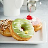 Assorted glazed fried donuts on a plate Royalty Free Stock Images