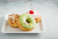 Assorted glazed fried donuts on a plate Stock Photos