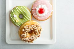 Assorted glazed fried donuts on a plate Royalty Free Stock Photos