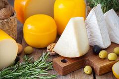 Assorted gourmet cheeses, olives, nuts and rosemary. Royalty Free Stock Photo