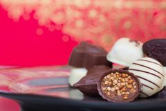 Assorted gourmet chocolate candies in the dish. royalty free stock photography