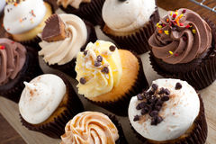 Assorted Gourmet Cupcakes. Close up of some decadent gourmet cupcakes frosted with a variety of frosting flavors stock photo