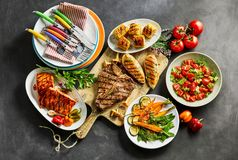 Assorted gourmet meat, foods and dining crockery stock image