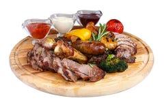 Assorted a grillé la viande avec les légumes cuits au four sur un conseil en bois photographie stock