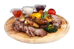 Assorted grilled meat with baked vegetables on a wooden board stock photography