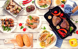 Assorted grilled meats with vegetables on a white wooden table. royalty free stock images