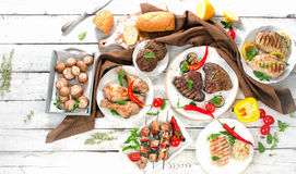 Assorted grilled meats and vegetables on  wooden background. Royalty Free Stock Image