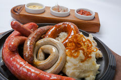 Assorted grilled sausages with mashed potatoes Royalty Free Stock Images