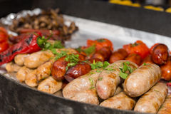 Assorted grilled sausages on a metal tray Stock Images