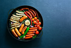 Assorted grilled sausages in a pan royalty free stock image