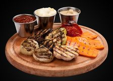 Assorted grilled vegetables on a wooden board. On dark background stock image