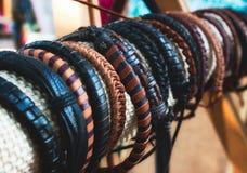 Assorted handmade genuine leather bracelets on display for sale. Assorted handmade genuine leather braided bracelets on display for sale stock image