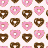 Assorted heart shaped doughnuts. Glazed with chocolate and pink icing topped with colourful sprinkles arranged in a seamless background pattern of repeat rows Royalty Free Stock Photography