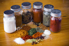 Assorted herbs and spices with glass containers. Mixed herbs and spices arranged on a wooden table Royalty Free Stock Photo