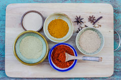 Assorted hot spicy powders in ceramic bowls Stock Photos