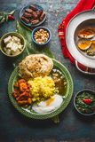 Assorted indian food. Bowls with paneer cheese , curries, rice, naan bread, samosas, chicken,chutney and spices on dark rustic bac Stock Photography