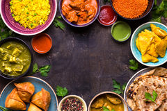 Assorted indian food. On dark wooden background. Dishes of indian cuisine. Curry, butter chicken, rice, lentils, paneer, samosa, naan, chutney, spices. Space Stock Image