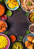 Assorted indian food. On dark wooden background. Dishes of indian cuisine. Curry, butter chicken, rice, lentils, paneer, samosa, naan, chutney, spices. Space Royalty Free Stock Images