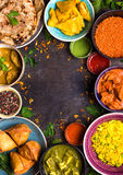 Assorted indian food. On dark wooden background. Dishes of indian cuisine. Curry, butter chicken, rice, lentils, paneer, samosa, naan, chutney, spices. Space Royalty Free Stock Photos