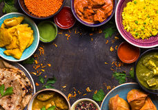 Assorted indian food. On dark wooden background. Dishes of indian cuisine. Curry, butter chicken, rice, lentils, paneer, samosa, naan, chutney, spices. Space Stock Images
