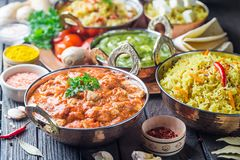 Assorted indian food. Different bowls with assorted indian food on dark wooden background. Dishes and appetizers of indian cuisine. Chicken, curry rice, lentils royalty free stock photos