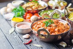 Assorted indian food. Different bowls with assorted indian food on dark wooden background. Dishes and appetizers of indian cuisine. Chicken, curry rice, lentils stock image