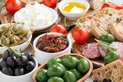 Assorted Italian antipasti - olives, salami, pickles and bread Royalty Free Stock Image