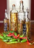 Assorted hot peppers and glass vinegar bottles royalty free stock photo