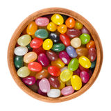 Assorted jelly beans in wooden bowl on white background Stock Photography