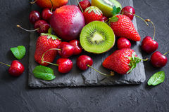 Assorted of Juicy summer fruits and berries. Strawberry, cherry, kiwi and peaches on black slate plate. stock photo