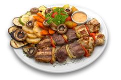 Assorted kebab: veal, chicken and pork. With grilled vegetables and mushrooms, served on the plate with special rose sauce royalty free stock photos
