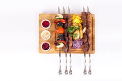 Assorted kebabs on a board white background, food Stock Photos