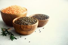 Assorted lentils. Marble, red and black raw organic lentils in wooden bowls with rosemary on grey concrete background. Copy space Royalty Free Stock Image