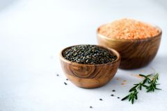 Assorted lentils. Marble, red and black raw organic lentils in wooden bowls with rosemary on grey concrete background. Copy space Stock Photo