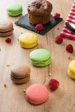 Assorted macaroons and cake on wooden table Stock Photography