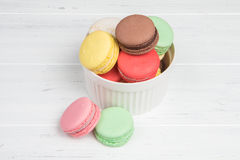 Assorted macaroons in white ceramic bowl on wooden table Stock Photo