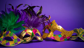 Assorted Mardi Gras or Carnivale mask on a purple background. Festive Grouping of mardi gras, venetian or carnivale mask on a purple background royalty free stock image