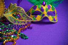 Assorted Mardi Gras or Carnivale mask on a purple background. Festive Grouping of mardi gras, venetian or carnivale mask on a purple background royalty free stock images
