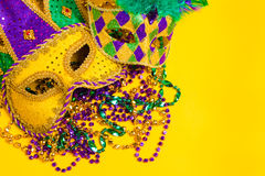 Assorted mardi gras mask on yellow with beads Stock Photos